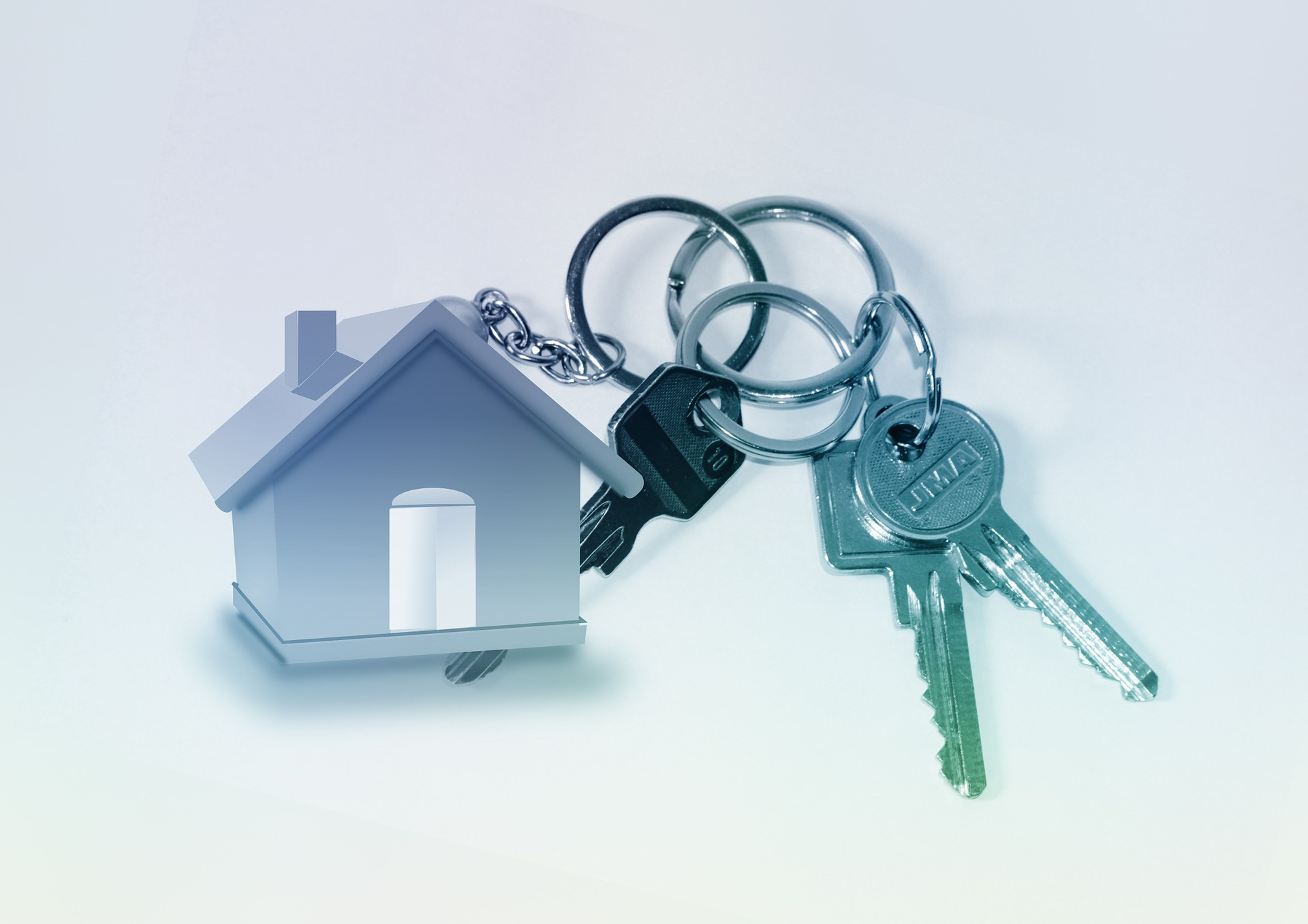 Ein Haus als Schlüsselanhänger an einem Schlüsselbund als Symbol für Gebäudesicherheit